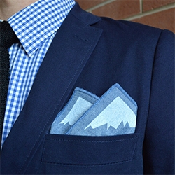 "The Outside/Inside pocket square features mountain peaks.  The words ""I'm always outside on the inside"" were hand-lettered by 16-year-old Mark van Leeuwen. Concept from Illustrator Samuel Ho."