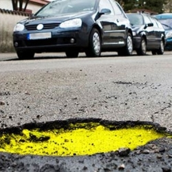 "Domenico Diego and Cristina Corradini designed the ""Street Safe Initiative,"" a brightly-coloured layer of asphalt a few inches beneath the surface of the road, which becomes visible when the road surface breaks up, making potholes easier to see."