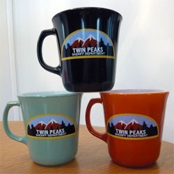 "TWIN PEAKS 20th Anniversary Art Exhibition means prop reproductions like Twin Peaks Sheriff Department mug, Double R Diner mug, and ""Fire Walk with Me"" Laura / Doorway photograph."