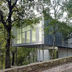 Agron Cultural center in the trees. A building of zinc adapting to ground in a small forest