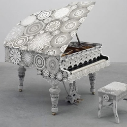 joana vasconcelos is a paris born artist working in lisbon who creates sculptures and installations by applying white crochet patterns to objects like computers, sculptures and pianos