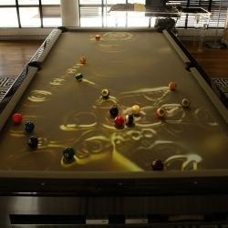 The CueLight uses a conventional pool table as it's canvas and the paint brush is an overhead projector equipped with sensors and motion detectors. The projector creates images on the pool table based on how the game is played