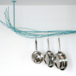 The Merkled Pot Rack is made of salvaged steel loom ends collected from a weaving company near the Merkled studio in Portland, Oregon.  Holds the lightest whisk to the heaviest cast iron skillet, in ice blue, burnt orange, and white.