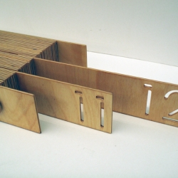 Qaa'im A. Goodwin releases photos of an office calendar entitled T.I.M. A Compositional Calendar System, this piece is made out of wood with what look like stencil-cut numbers to denote the current month and day.