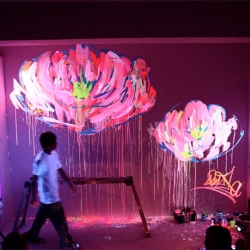 Que Houxo is a Japanese artist who does live paintings. His style is quite colorful, he uses fluorescent paints with black lights.