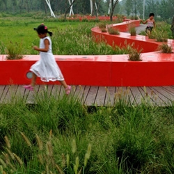 The Red Ribbon Park in China's Qinhuangdao City by Turenscape Landscape Architects winds along a verdant riverside.