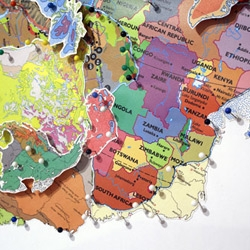'Find your Way' is a series of maps by artist Rebecca Ross, painstakingly pinned and layered, country over continent, color over shape.