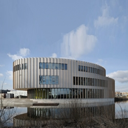 Overlapped circular plans result ona  dynamic building sitting in front of the water, for the new Bijlmer Park Theater by Paul de Ruiter in Amsterdam.