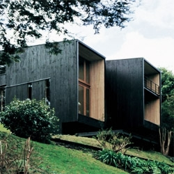 House at Lago Rupanco, by Beals Arquitectos in the chilean south forest.  It's made out of wood, painted black on the outside,  making  the house disappear into the forest.