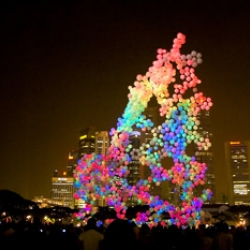 The Burble is a massive structure reaching up towards the sky, composed of approximately 1000 extra-large helium balloons each of which contains microcontrollers and LEDs that create spectacular patterns of light across the surface of the structure.