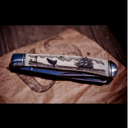 The CXXVI Scrimshaw Knife is hand etched in a small workshop in Maine, this seascape scrimshaw is laid into the bone with black India ink and sealed with a double dose of wax to protect the design and handle.
