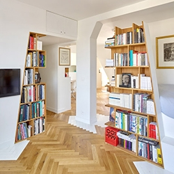 h2o Architectes renovated a lovely apartment in the Arsenal district of Paris with amazing slanted wooden bookshelves fitted into every nook!