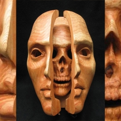 Woodsculpter / Painter Anthony Santella presents a mask in wood. Blank stare outside, hinged inside with a lovely skull. Not for your everyday masquerade.