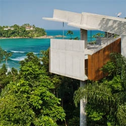 A concrete house floating in the middle of Rio de Janeiro's forest, designed by local architects SPBR. Thanks to a series of concrete structural elements, the house is lifted to enjoy one of the most impressive views over the sea.