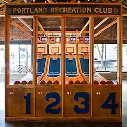 At Spirit of 77 sports bar in Portland, OR, a hand-built basketball arcade was made with the repurposed high school gymnasium flooring.