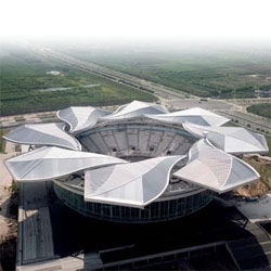 Qi Zhong Stadium in Shangai will host the Tennis Masters Cup once again. Shapped like a magnolia, its roof opens completly to regulate natural ligthing.  Check out the video too.