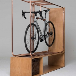 Made of copper pipes, oiled Tuscan leather, and Scottish oak, the Stasis bike storage suspends a bicycle above a small shelf and basket.
