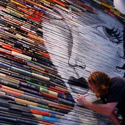 mike stilkey paints on stacks and stacks of books