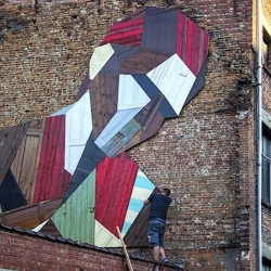 Elsewhere – recycled wood mural by Strook for Mechelen Muurt. The mural is placed on the side wall of an old furniture factory in Mechelen, Belgium. It's made by piecing together discarded wooden planks, doors and furniture.