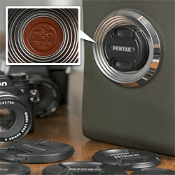 "Emissary Camera Bag has a fascinating lens cap holder - ""The lens cap mount holds 77mm, 72mm, 67mm, 62mm, 58mm, 52mm, 49mm, 46mm, 41mm and 37mm lens caps, and can hold up to three lens caps at one time."""