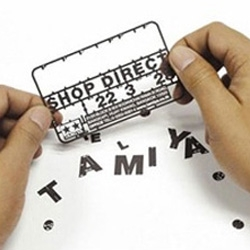 This business card can be used to create tiny plastic models. It's designed as a sample modeling kit. You can build a toy plane, boat, or car from the pieces.