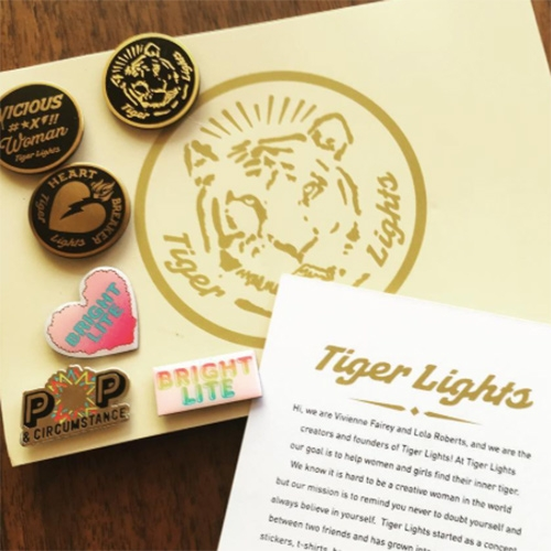 "Tiger Lights Creative! Fun pins and tees. ""We know it is hard to be a creative woman in the world but our mission is to remind you never to doubt yourself and always believe in yourself"" Project by Vivienne Fairey and Lola Roberts."