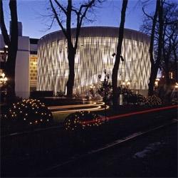 Tivoli Concert Hall by 3XN, in Copenhagen, Denmark. A round building with a light skin.