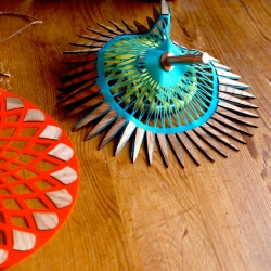 These lasercut fabric + wood spinning tops create mesmerizing movements when spun, by Rachel Gant.