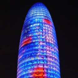 Barcelona's 38-story Agbar office tower is wrapped in over 4,500 LED luminaires which enrobe the missile-shaped structure in colored light.
