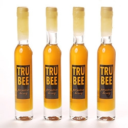 TruBee Honey 9 oz. of premium raw honey in an Italian glass ice wine bottle, with the top and neck of the bottle hand dipped in pure, unbleached beeswax. TruBee honeys capture the essence of a particular region and season.