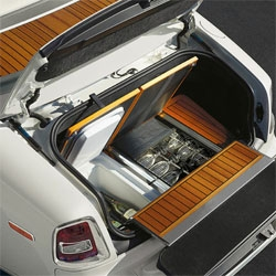 Pop open the trunk of the 2012 Rolls Royce Phantom Drophead Coupé to find yacht inspired teak flooring hiding a mini fridge, custom glasses, and a bench seat for two...