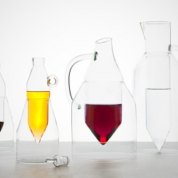 Inspired by how the ritual of drinking with others raises the spirit, designer Dean Brown created the Uplifting Carafe collection.  The center of the carafe lifts out, while the outer vessel rests on the table serving as a stand.