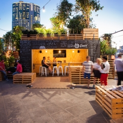 Australian design firm HASSELL's Urban Coffee Farm consists of more than 120 coffee plants, shipping containers – housing the 'Brew Bar' – and timber pallets in Melbourne.