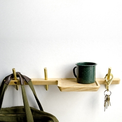 """Dixon Branded's Intersect is a series of wall hooks and shelves made from Ash and Brass. Installing with minimal hardware, the series utilizes this """"intersection"""" of brass and wood to maintain a strong hold with the wall."""