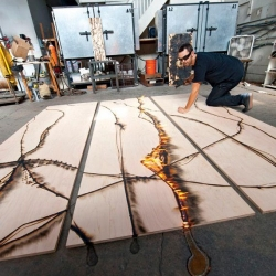 Jonah Ward isn't a pyro, but he does burn wood on a daily basis. The Oakland-based California artist creates stunning wood panels that have been charred and burned by molten glass that he pours, drips, and drizzles over planks of woods.