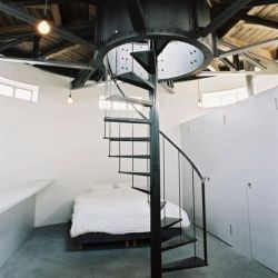 zecc architekten converted an unused water tower into an amazing minimalist home. Shown is one of the bedrooms up top.