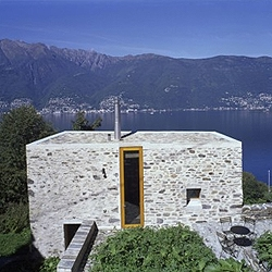 A beautiful stone house, acting as an ancient wall. The monolithic volume is open on strategic points to enjoy the great views over the lake. By Wespi de Meuron.