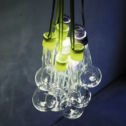 The LED-lamp WRAPPED GLASS was inspired by the Czech Sumperak House, whose architecture recalls a modernist style, an untypical design for the 1960s. Bundle of 10 laboratory glasses, equipped with 10 LED