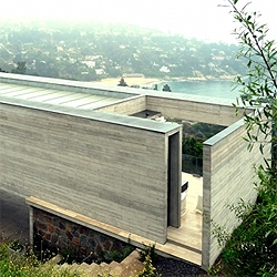 A concrete house on the chileab beach side. The planes of the house frame the landscape with amazing views.